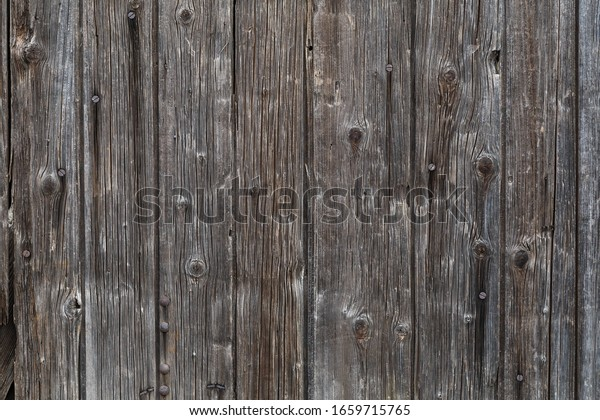A ruined wood door made with vertical boards, in time this wood became black color.