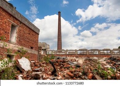 Ruins of abandoned and dilapidated factory overgrown of vegetation