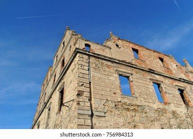 Ruins of abandoned palace or manor house, broken windows with sky, forgotten place turned into ruins. Devastated walls, bullets traces. Bricks and stones.