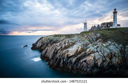 The ruins of the abbey of Saint-Mathieu de Fine-Terre and the lighthouse in the sunset, Finistere, Brittany, France