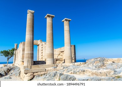 Ruins of the ancient acropolis temple building in the greece city of lindos rhodes on a sunny day with plain blue sky background