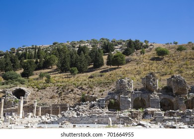Ruins of the ancient city of Ephesus at the foot of a hill overgrown with grass and trees in a summer sunny day