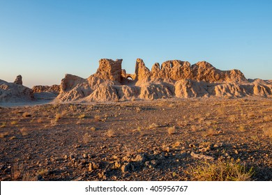 The ruins of the ancient fortress of Ayaz-Kala at dawn. Pass the remains of old mud walls and the desert. All this against the background of blue sky