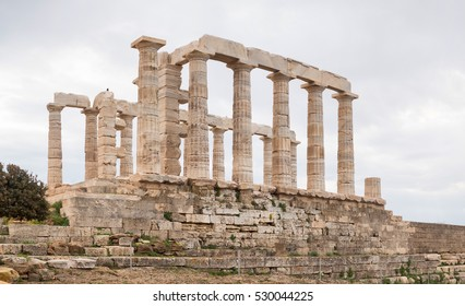 Ruins of an ancient Greek temple of Poseidon under dramatic cloudy sky, Cape Sounion, Greece