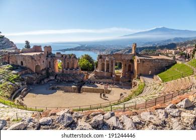 Ruinen des alten griechischen Theaters von Taormina, Sizilien der Ätna mit seinem doppelten Rauch Schwanz im Hintergrund über der Morgensonne beleuchtete Giardini-Naxos Bucht des Ionischen Meeres.