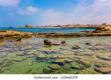 Ruins of the ancient port of Caesarea. Flooded in the sea remains of fortifications. Spring day in Israel. Concept of archeological and historical tourism