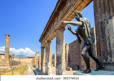 Ruins of the antique Temple of Apollo with bronze Apollo statue in Pompeii, Naples, Italy. Pompeii was destroyed by Vesuvius eruption in 79 AD.