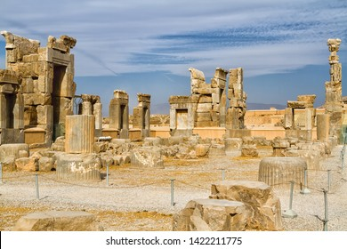 Ruins of Apadana and Tachara Palace behind stairway with bas relief carvings in Persepolis UNESCO World Heritage Site against cloudy blue sky in Shiraz city of Iran. Middle East, Asia