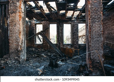 Ruins of burned brick house after fire disaster accident. Heaps of ash and arson, burnt furniture, collapsed roof, broken windows