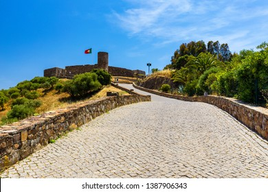 Ruins of Castle in Aljezur with waving portuguese flag, Algarve, Portugal. Aljezur castle, Portugal Arabian gorgeous castle, made of stone with a tower. Aljezur, Algarve, Portugal.