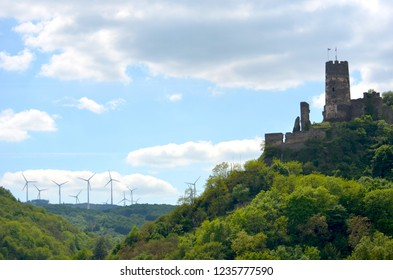 The ruins of a castle are on top of a forest covered hill. Flags are on castle tower. On a distant hill are wind turbines. The sky is blue with white and grey clouds.