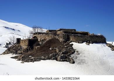 Ruins of castle and snow near Kadisha valley