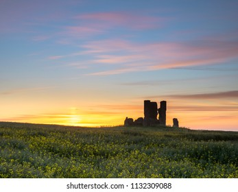 The ruins of the church of St James surrounded by oil seed rape at sunrise.