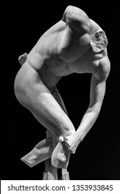 Ruins of classical roman statue showing male nude body - black and white photo