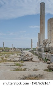 Ruins of colonnaded antique street with marble columns, paved with huge stone plates, and damaged Corinthian capital during the daytime. Side, Turkey   - Shutterstock ID 1987632167