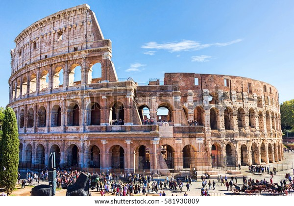 Ruins of the colosseum in Rome, walking visitors and tourists, sunny day with blue sky, Italy
