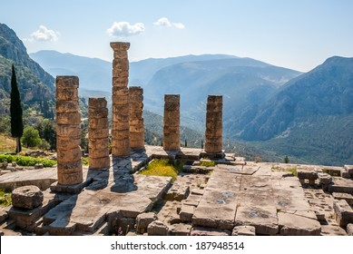 Ruins and columns of an ancient greek temple in front of the surrounding mountains