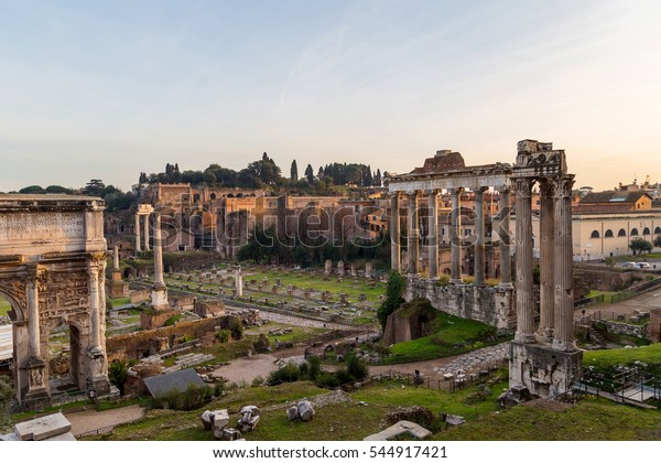 Ruins and columns of Roman Forum in warm light of sunset in Rome, Italy. Popular touristic destination and site. Ruins of Temple of Saturn.