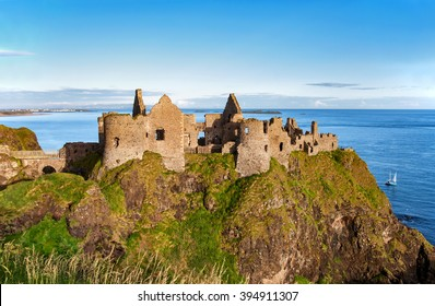 Ruins of Dunluce castle in County Antrim, Northern Ireland, UK, with the far view of  Portrush resort on the left