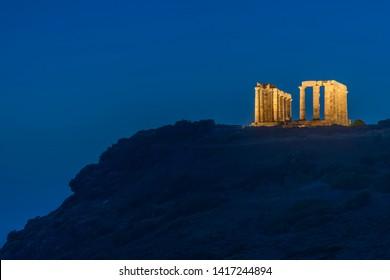 ruins of greek temple in night lights under night sky