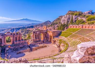 Ruinen des griechischen Theaters von Taormina und die malerische Bergkette vom Vulkan Ätna bis Castelmola im Hintergrund. Taormina, Sizilien, Italien