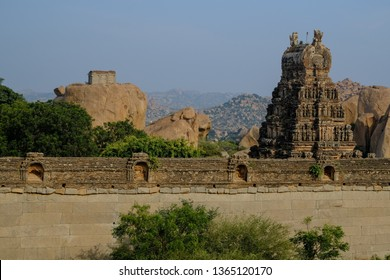 a ruins of hindu temple in hampi with temple wall and gopuram