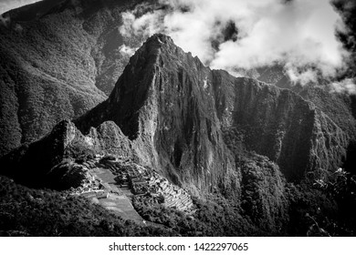 The ruins of machu picchu taken in Black and White from a distant view.