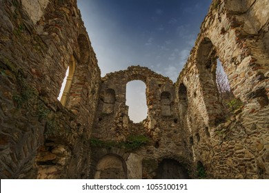 Ruins of the medieval Byzantine fortified castle town of Mystras, Greece. Old historical stone buildings and walls with traditional arches in Mystras castle town. Laconia, Peloponnese, Greece.