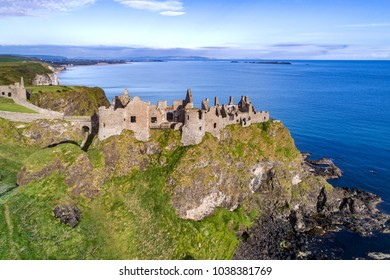 Ruins of medieval Dunluce Castle, cliffs, bays and peninsulas. Northern coast of County Antrim, Northern Ireland, UK. Aerial view.