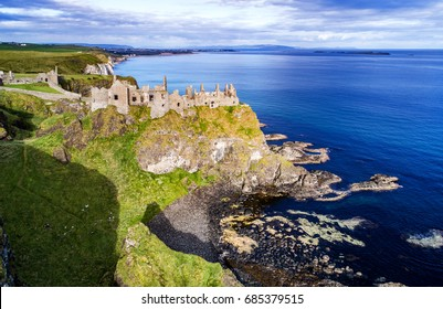 Ruins of medieval Dunluce Castle, cliffs, bays, peninsulas and islands.    Northern coast of County Antrim, Northern Ireland, UK.  Far Portrush resort in the background. Aerial view.