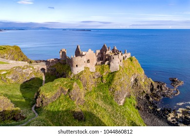 Ruins of medieval Dunluce Castle on a steep cliff. Northern coast of County Antrim, Northern Ireland, UK. Aerial view.