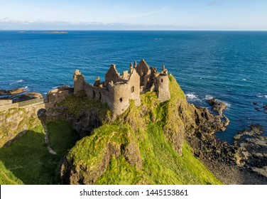 Ruins of medieval Dunluce Castle on a steep cliff. Northern coast of County Antrim, Northern Ireland, UK. Aerial view in sunrise light