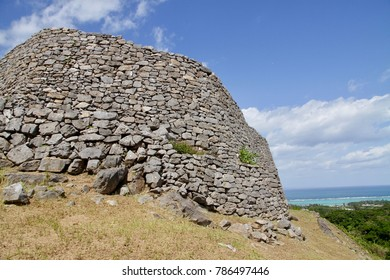 The ruins of Nakijin Castle in Okinawa, Japan. The UNESCO world heritage and the hundred selected castle in Japan. The straw field, blue sky with white clouds landscape.