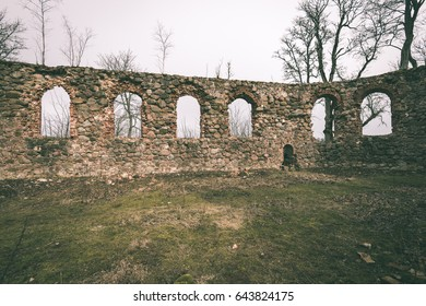 ruins of old abandoned church with red bricks and stone in early spring in Latvia - vintage green look