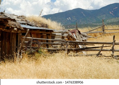 The ruins of an old ranch in southwestern Utah, with distressed old wooden fencing a dramatic sky and a mountain range in the background
