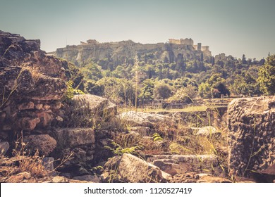 Ruins on the Agora overlooking famous Acropolis hill, Athens, Greece. Panoramic scenic view of the Athens historical center. Ancient Greek Agora is one of the main tourist attractions of Athens.