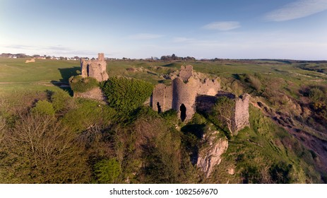 The ruins of Pennard castle on the Gower peninsula in Swansea, South Wales, UK, overlooking Three Cliffs Bay with Pennard Golf Club in the background.