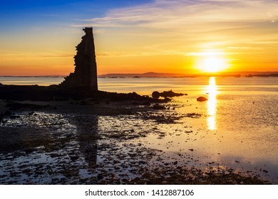 Ruins of Saint Saturnino tower in Cambados city at golden sunset with Arousa estuary at background