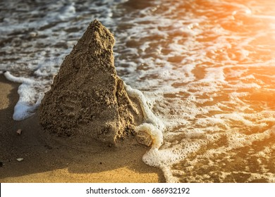 The ruins of a sand castle being swept away by the sea