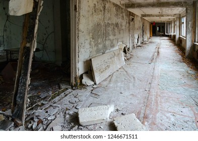 Ruins of school corridor in abandoned building, dead ghost town Pripyat in Chernobyl NPP alienation zone, Ukraine