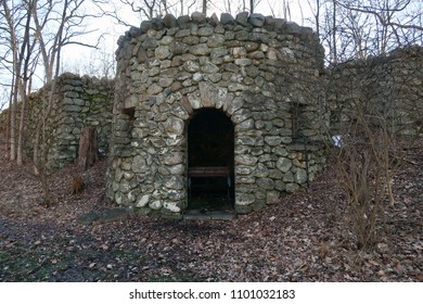 Ruins of a stone structure in the woods with an opening for a door.
