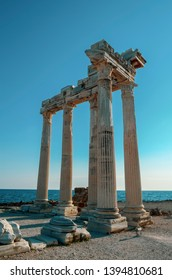 The ruins of the Temple of Apollo in ancient sity of Side in Turkey against a blue sky and sea.