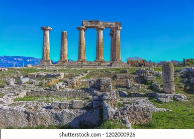 Ruins of Temple of Apollo in Corinth Greece standing up on a hill with remenants of rock walls scattered about under a bright sun with mountians and a blue sky behind