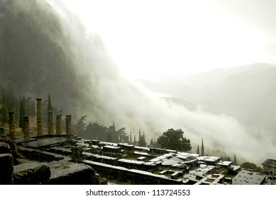 Ruins of the Temple of Apollo at Delphi, Greece in a rainstorm with clouds rolling down the valley