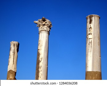Ruins of three columns against blue sky. Taken at the ancient city of Perge (near Antalya, Turkey). Mid-column is of corinthian order, two columns have bas reliefs.