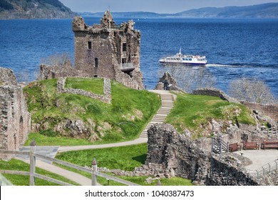 Ruins of Urquhart Castle against boat on Loch Ness in Scotland