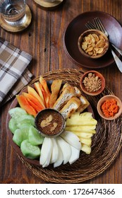 Rujak Buah, or Fruity Rojak on Plate Presentation. Indonesia Local Food, Made from Fresh Fruit and Fried Tofu, Served with Palm Sugar and Peanut Sauce. Garnished with Fried Garlic. Top View.