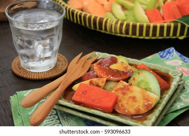 Rujak Buah. Javanese fresh fruit salad with spicy, sweet and tangy sauce; plated on a small ceramic plate on a folded batik napkin. A glass of water left nearby. The fruit tray is in the background.
