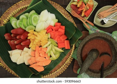 Rujak Buah. Javanese fresh fruit salad with spicy, sweet and tangy sauce. The fruits are arranged on a traditional bamboo tray lined with banana leaf. The sauce is served on a stoneware mortar.