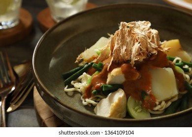 Rujak Juhi or Mie Juhi. Salad of yellow noodles, cooked vegetables and crispy grilled cuttlefish crackers with peanut dressing from Betawi, Jakarta.